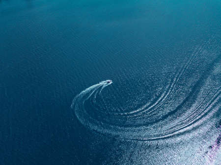 Aerial drone view of speed boat in motion, transportation concept, summer time