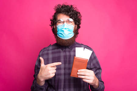 Photo of curly man wearing medicinal mask and pointing at passport with avia tickets
