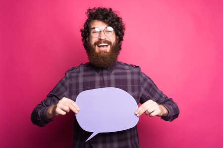 Portrait of happy young man wearing eyeglasses and holding speech bubble