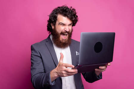 Photo of shocked bearded man in casual looking at laptop
