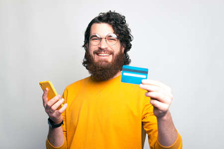 A young bearded man is holding a credit card and his phone looking at the cmera is smiling
