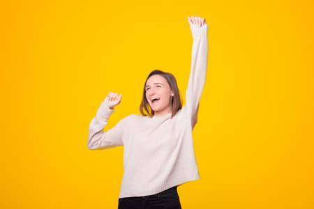 Photo of amazed young girl standing over yellow background celebrating victory fists up