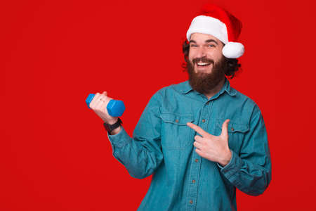 Young bearded man suggests to go to the gym while wearing christmas hat and pointing at a dumbbell
