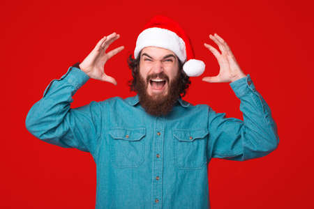 Mind blowing gesture is made by a young bearded man wearing a christmas hat.