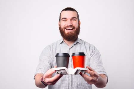 A cheerful bearded young man is holding a set of two hot drinks in papper cups and looking at the camera is smiling near a white wall