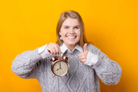 Smiling young woman holding alarm clock and showing thumb up Banque d'images