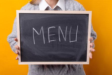 Girl holding a small blackboard with menu word written on it.