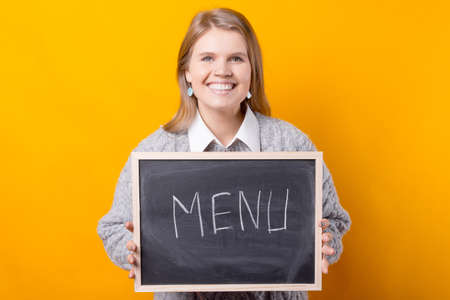 Photo of a woman holding a blackboard with the word menu written on it