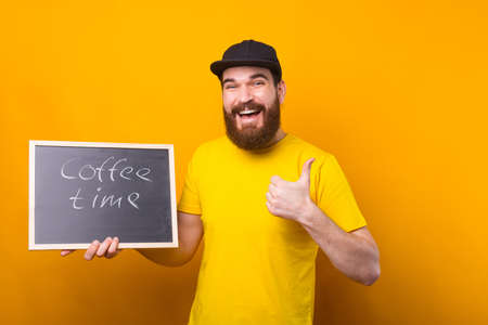 A man smiling is holding a black board with coffee time written on it