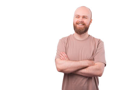 Portrait of charming young bearded man looking away with crossed arms over white background 写真素材