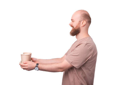 Cheerful bearded hipster man giving someone two paper cups of coffee