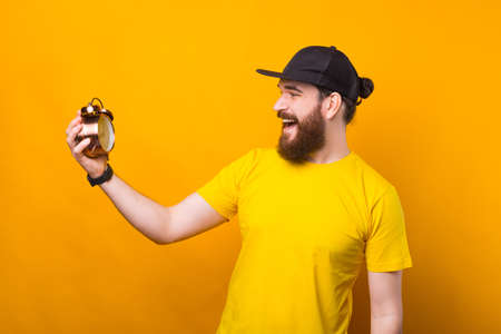 Bearded hipster man looking at alarm clock over yellow background