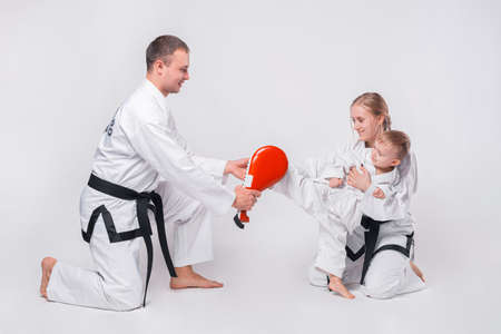 Young family with their little boy practicing martial arts over white background