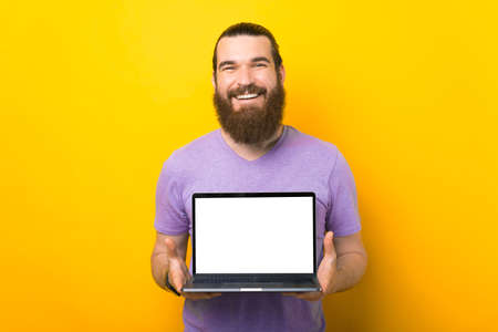 Wonderful bearded man is holding a blank screen laptop to the camera.
