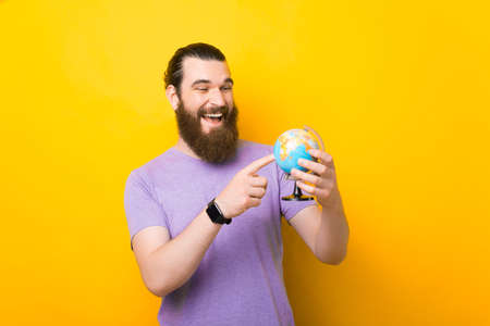 Smiling man is pointing on a small globe over yellow background. Standard-Bild