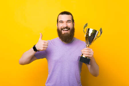 Cheerful male hipster is holding a trophy and showing like gesture.