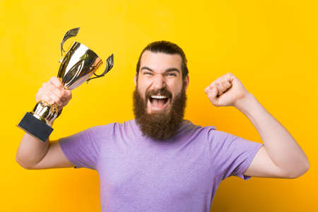 Screaming bearded man is making the winner gesture and holding a trophy.
