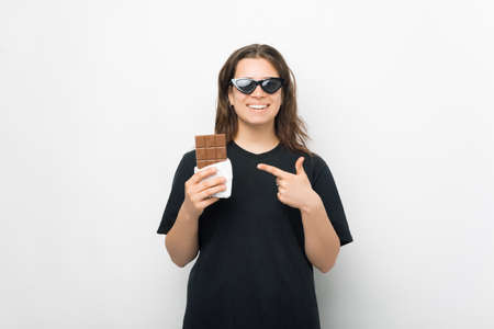 Smiling girl is pointing at a bar of chocolate. Standard-Bild