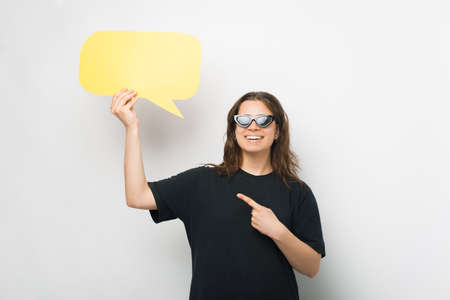 Gorgeous young woman is pointing at the speech bubble she is holding.