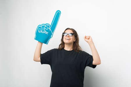 Young woman is wearing sunglasses, foam fan glove and making the winner gesture.