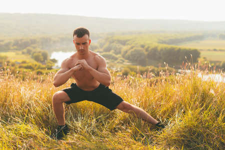 Young strong man is stretching outdoors in the nature.