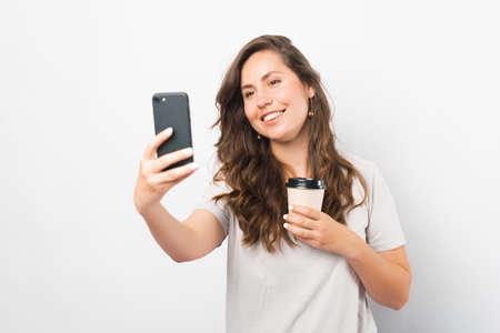 Joyful young woman is taking a selfie while holding her take away cup of coffee.