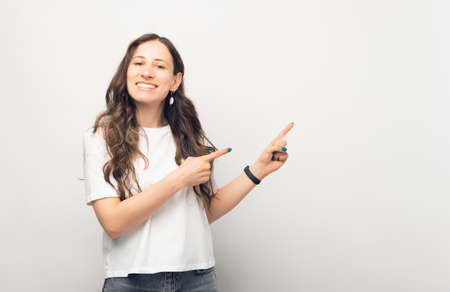 Young female is pointing with both hands aside over white background.