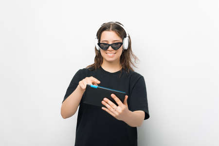 Smiling girl listening to the music is playing on her tablet on white background. Standard-Bild