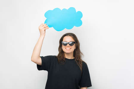 Young woman wearing sunglasses is holding a paper cloud above her head.