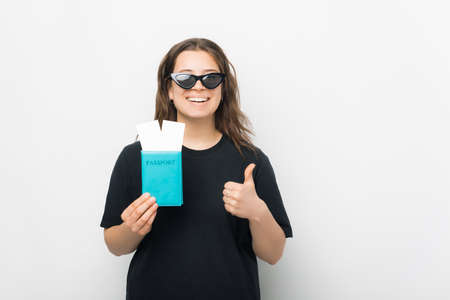 I like traveling. Young smiling woman is holding a passport with two tickets and thumb up. Standard-Bild