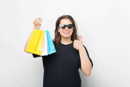 Smiling young woman is holding some shopping bags and shows thumb up.