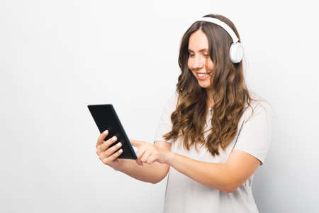 Girl dressed in white enjoys using her tablet while she is listening to the music.