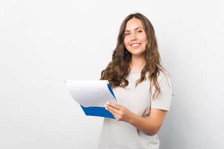 Portrait of a smiling woman holding a clipboard over white background.