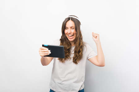 Cheerful girl has won in betting or gaming on her tablet. Standard-Bild