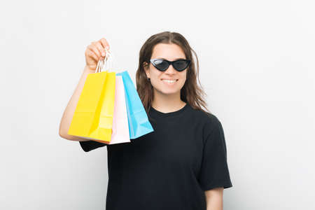 Pleased young woman is holding some shopping bags over white background.