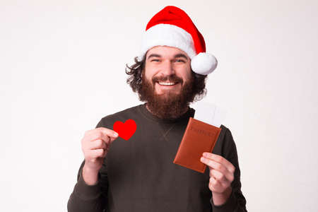 I just love traveling. Bearded man is holding his passport with tickets and heart shape.