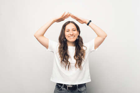 Cheerful young woman is making the roof gesture over white background.