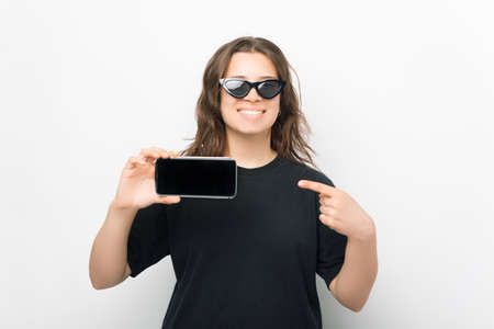 Pretty smiling woman is pointing at the screen of the phone she is holding.