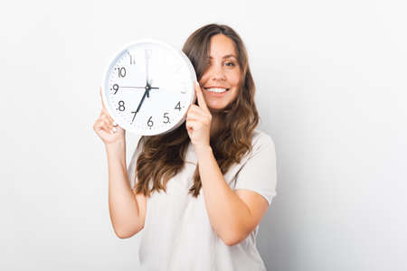 Young woman is holding a white clock in a studio.