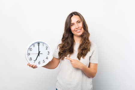 Portrait of a young woman pointing at a clock she is holding. Standard-Bild