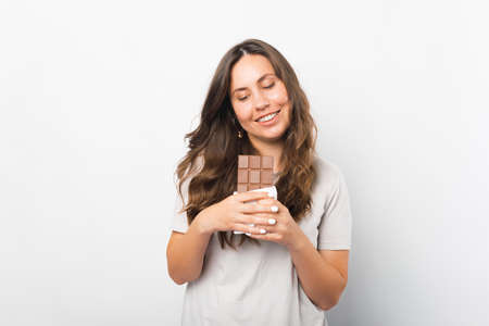 Young woman is tempted to bite a piece of chocolate she is holding. Standard-Bild