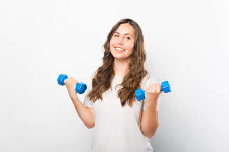 Young bright girl is lifting up two dumbbells over white background.