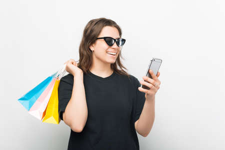 Smiling girl wearing sunglasses is ordering something online by her phone.