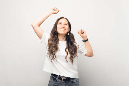 Excited young woman is making the winner gesture while looking up.