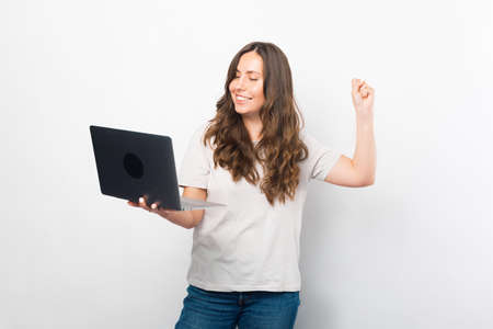 Gorgeous young woman is making the winner gesture while holding a laptop. Standard-Bild