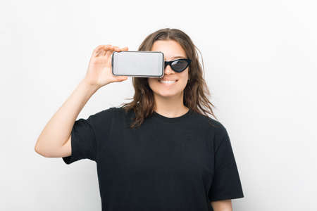 Smiling woman covers one eye with her phone while standing over white background.