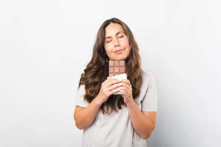 Portrait of a woman with eyes closed enjoying the smell of chocolate. Standard-Bild