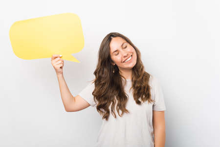Young smiling woman with eyes closed is holding a yellow speech bubble.