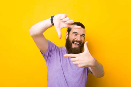 Cheerful young man is making the frame gesture over yellow background. Standard-Bild
