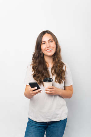 Vertical photo of a young woman holding her phone and a cup of coffee to go. Standard-Bild